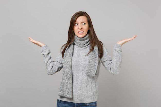 Verbijsterde jonge vrouw in grijze trui, sjaal opzoeken verspreiding wijzende handen opzij geïsoleerd op grijze achtergrond. gezonde mode levensstijl mensen emoties, koude seizoen concept. bespotten kopie ruimte.