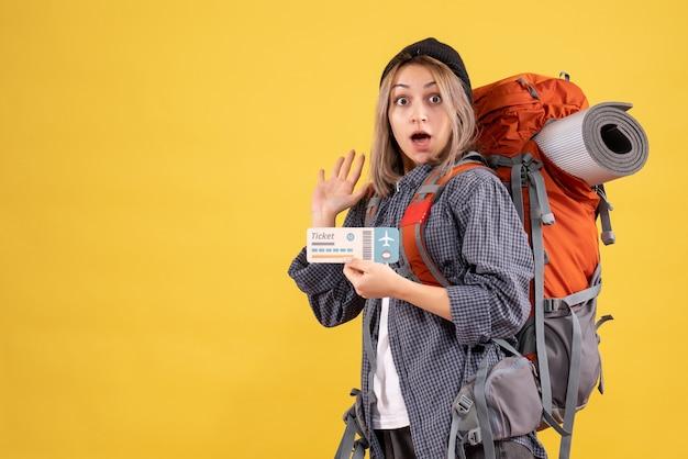 Verbijsterde reiziger vrouw met rugzak met ticket