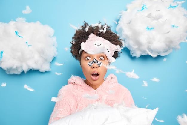 Verbijsterde vrouw met krullend haar past applicatormasker toe op gezicht probeert mee-eters en poriën te verwijderen gekleed in nachtkleding slaapmasker op voorhoofd naar bed gaan houdt zacht kussen vast tegen blauwe studiomuur