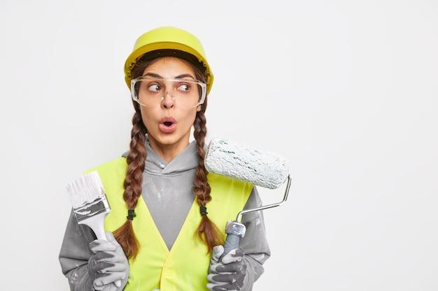 Verbijsterde vrouwelijke decorateur bezig met het repareren van binnenmuren met kwast en roller