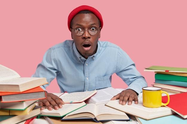 Verbijsterde workaholic in rode hoofddeksel, bril en formeel overhemd, staart met een angstige gezichtsuitdrukking, houdt de handen op schoolboeken