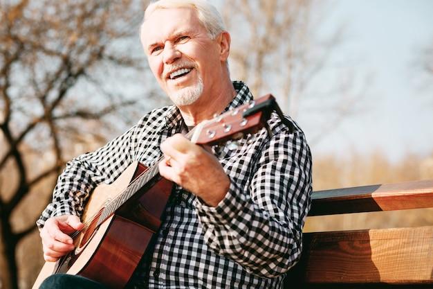 Verbinding via muziek. lage hoek van enthousiaste volwassen man zit in het park en geniet van gitaarspel