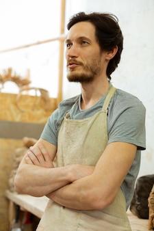 Verblijf in werkplaats. kortharige vastberaden man in vuile schort klaar voor actieve dag in aardewerkstudio
