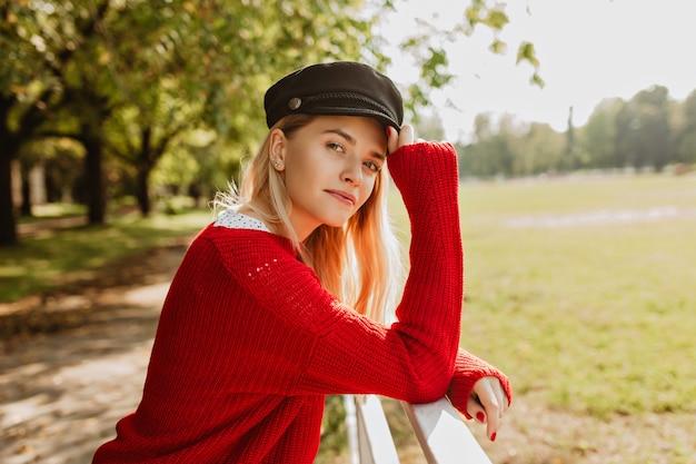 Verbluffende blonde die buiten geniet van zonnig weer. mooi meisje in trendy rode trui ziet er goed uit in het herfstpark.