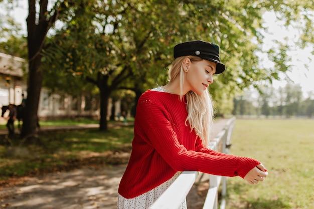 Verbluffende blondine met een elegante stijl die zich goed voelt buiten. charmant meisje poseren in de buurt van oud gebouw in het park.