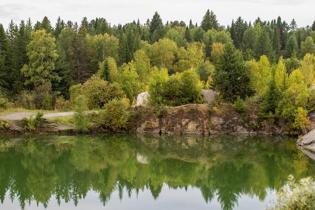 Verbluffende foto van herfstgebladerte weerspiegeld op een meer met een glasachtig spiegelwateroppervlak.