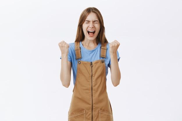 Verbluffende gelukkige jonge vrouw die wint, overwinning viert, ja tevreden schreeuwt