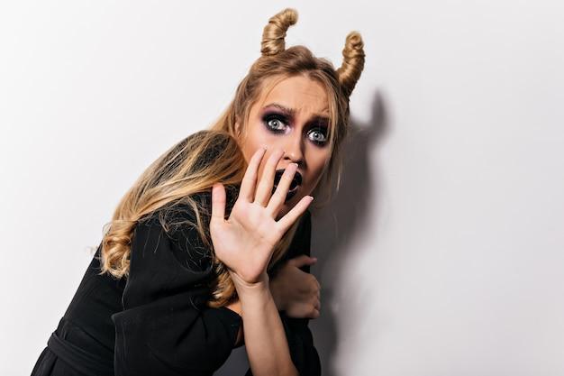 Verbluffende heks met grappig kapsel poseren met enge gezichtsuitdrukking. binnen schot van bezorgd vrouwelijk model dat halloween in vampierkostuum viert.