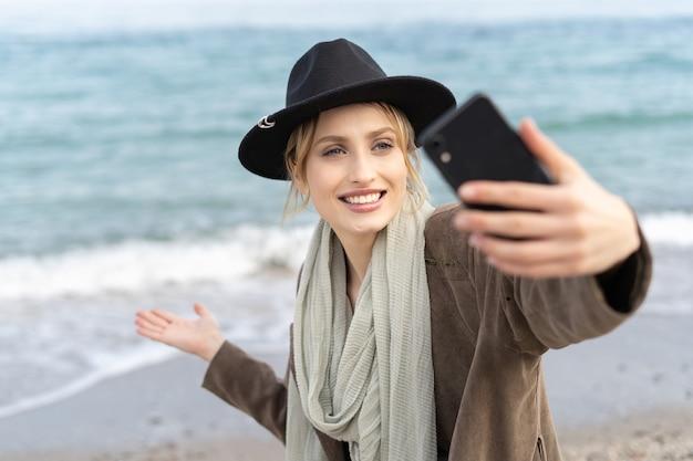 Verbluffende jonge vrouw neemt een selfie en toont prachtig strand met een grote glimlach met behulp van haar mobiele telefoon