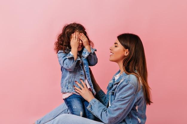 Verbluffende jonge vrouw speelt met preteen kind. studio shot van zorgeloze familie in denim kleding.