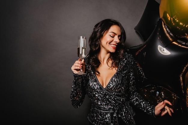 Verbluffende krullende vrouw die van champagne geniet