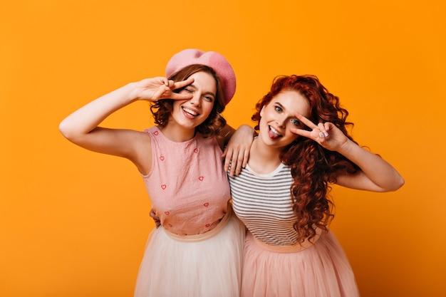 Verbluffende meisjes die en op gele achtergrond glimlachen gebaren. vooraanzicht van twee omhelzende vrienden die vredesteken tonen.