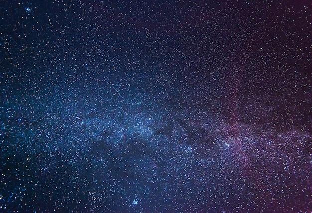 Verbluffende sterrenhemel op een wolkenloze winternacht te midden van een blauw-roze mist die boven de aarde gloeit