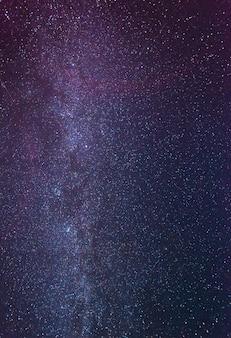 Verbluffende sterrenhemel op een wolkenloze winternacht te midden van een blauwroze mist die boven de aarde gloeit