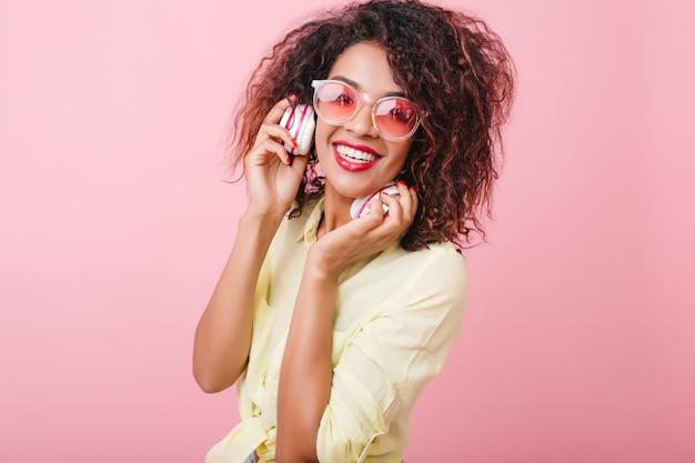 Verbluffende vrouw met lichtbruine glanzende huid ontspannen met favoriete muziek. portret van blij mulat meisje in trendy kleurrijke zonnebril luisteren muziek in koptelefoon.