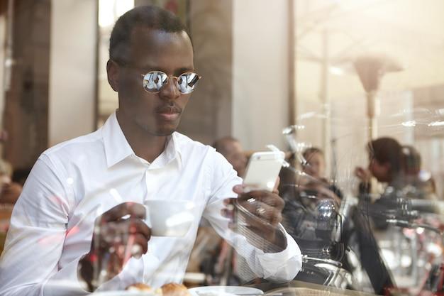 Verbonden blijven. kijk door vensterglas van knappe zwarte europese werknemer in tinten en formele shirt drinken koffie tijdens de lunchpauze en het controleren van e-mail op touchscreen mobiele telefoon
