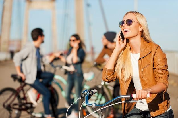 Verbonden blijven. mooie jonge lachende vrouw leunend op haar fiets en praten op de mobiele telefoon terwijl haar vrienden op de achtergrond staan standing