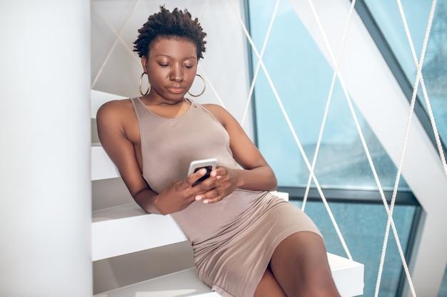 Verbonden. elegante knappe vrouw met een donkere huidskleur en een smartphone