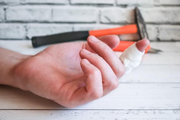 Verbonden vinger aan de hand van de meester. een ongeval op het werk - de gewonde vinger van de man verbinden.