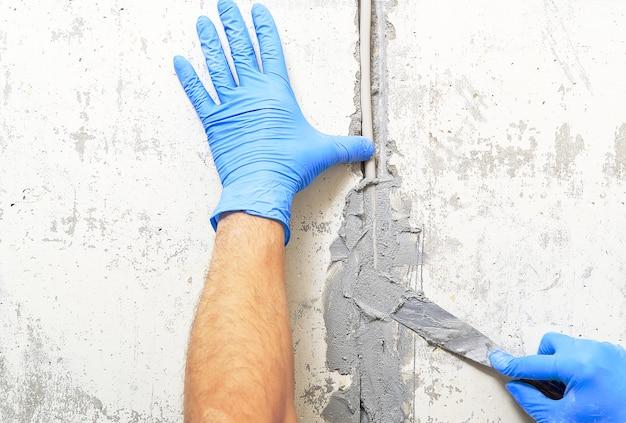 Verborgen installatie van elektrische draden voor stopcontacten op een betonnen muur.