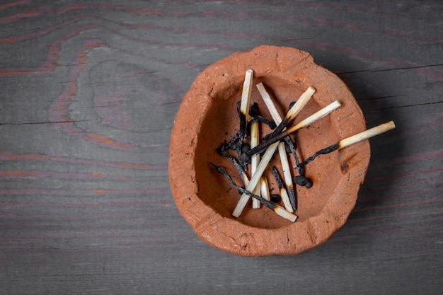 Verbrande houten lucifers liggen in een asbak van klei
