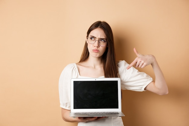 Verdacht fronsend meisje in glazen wijzend op laptopscherm, iets vreemds online laten zien, staande op beige achtergrond.