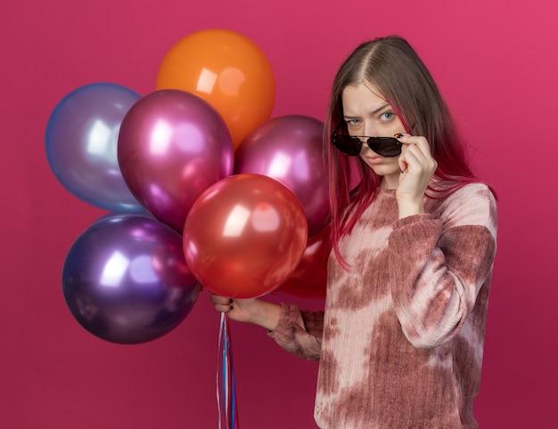 Verdacht jong mooi meisje met een bril met ballonnen geïsoleerd op roze muur