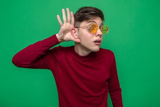 Verdacht toont luistergebaar jonge knappe kerel met een bril