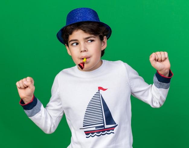 Verdacht uitziende kleine jongen met een blauwe feestmuts die een feestfluitje blaast en een ja-gebaar toont dat op een groene muur wordt geïsoleerd
