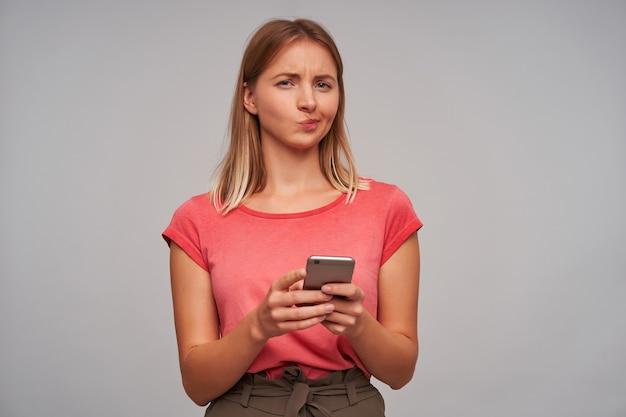 Verdacht uitziende vrouw, volwassen meisje met blond haar. ik draag een roze t-shirt en een bruine rok. met een smartphone. wantrouwen, geïsoleerd over grijze muur