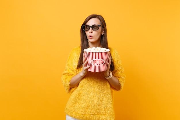 Verdacht verbaasd jong meisje in 3d-imax-bril kijken naar film kijken opzij met emmer popcorn geïsoleerd op felgele achtergrond. mensen oprechte emoties in de bioscoop, lifestyle concept.