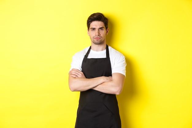 Verdachte barista loensend, armen gekruist op de borst en met ongeloof naar iets kijkend, staande over gele achtergrond.