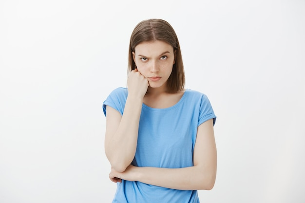 Verdachte en sceptische vrouw die een wenkbrauw optrekt en met ongeloof kijkt, twijfelt