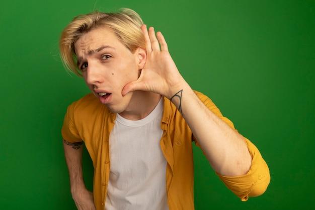 Verdachte jonge blonde kerel die gele t-shirt draagt die luistergebaar toont dat op groen wordt geïsoleerd
