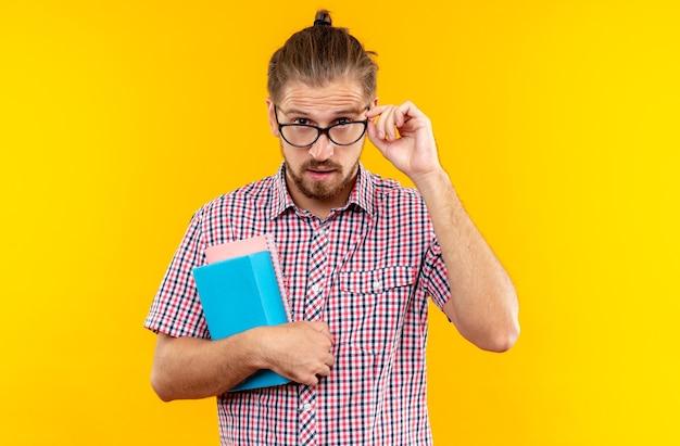 Verdachte jonge kerel student draagt rugzak met bril met boek geïsoleerd op oranje muur