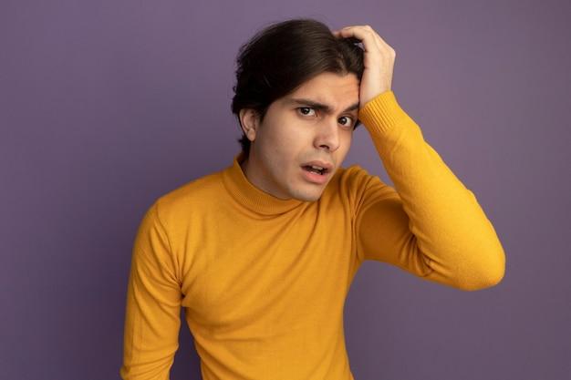 Verdachte jonge knappe kerel die gele coltrui draagt ?? die hand op hoofd zet geïsoleerd op paarse muur