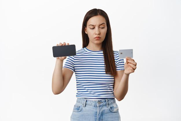 Verdachte jonge vrouw die twijfelt, horizontaal smartphonescherm toont, met ongeloof kijkt en wenkbrauw op creditcard zwaait, maakt zich zorgen, staande over witte muur.