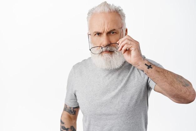 Verdachte oude man met tatoeages, bril af en kijken met ongeloof en boos gezicht, verward over iets vreemds, staande tegen de witte muur