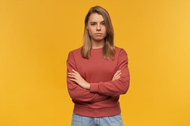 Verdachte peinzende jonge vrouw in terracotta sweatshirt met gekruiste armen en opgeheven voorhoofd geïsoleerd over gele muur