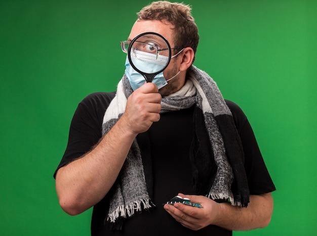 Verdachte zieke man van middelbare leeftijd met een medisch masker en een sjaal die pillen vasthoudt en naar de camera kijkt met een vergrootglas
