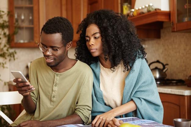 Verdachte zwarte vrouw probeert bericht te lezen dat haar gelukkige echtgenoot naar iemand op de mobiele telefoon stuurt omdat ze verraad vermoedt, hem niet vertrouwend. jaloezie, ontrouw en wantrouwen
