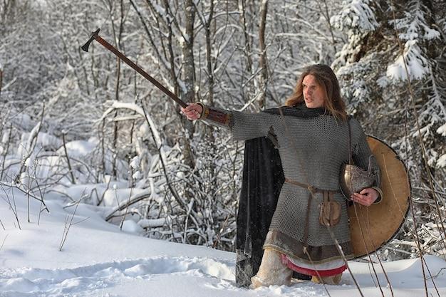 Verdedig de jonge krijger in maliënpantser gewapend met een zwaard en een bijl