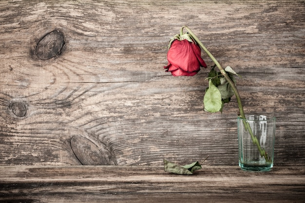 Verdorde gedroogde roos in glas op houten tafel