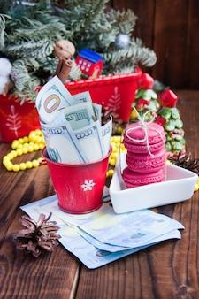 Verdraaide rekeningen van dollars en euro's in rode kerstmisemmer, euro en roze makarons
