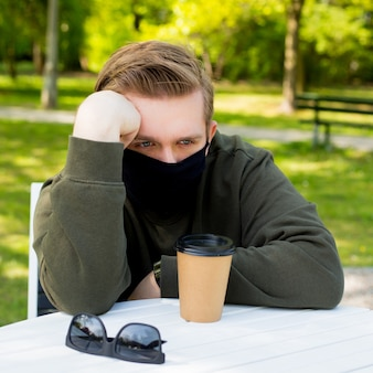 Verdriet man in een beschermend zwart masker zittend aan een tafel in een café. virusbescherming. mannen in een masker koffie drinken in een stadspark. kopieer ruimte.