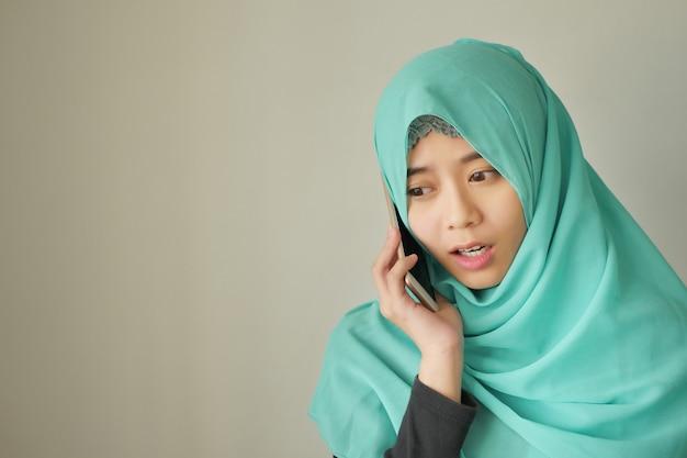 Verdrietig, boos, gefrustreerde moslimvrouw met smartphone