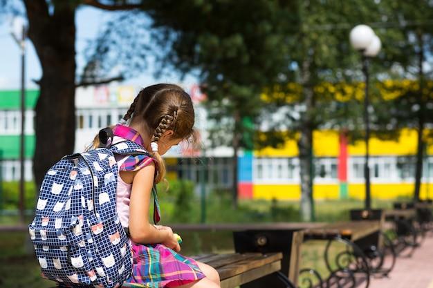 Verdrietig, boos meisje in de buurt van de school met een rugzak. vermoeidheid door lessen, wrok,
