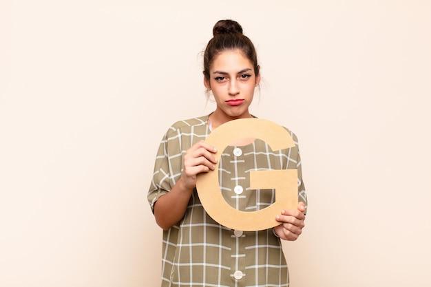 Verdrietig, depressief, ongelukkig, de letter g van het alfabet vasthoudend om een woord of zin te vormen.
