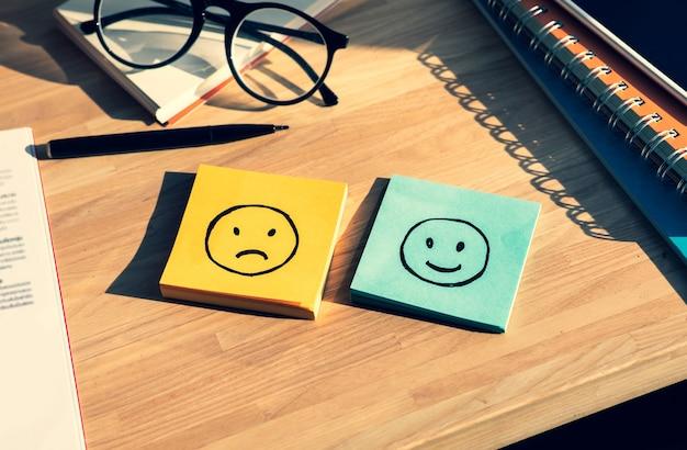 Verdrietig en blij gezicht op het papier