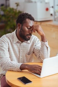 Verdrietig en moe. uitgeput, boos man zit aan de tafel in het café en werkt op de laptop terwijl hij de brug van zijn neus knijpt en er moe uitziet